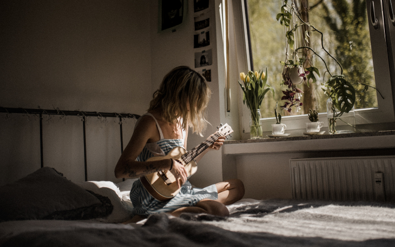 girl playing guitar in bedroom
